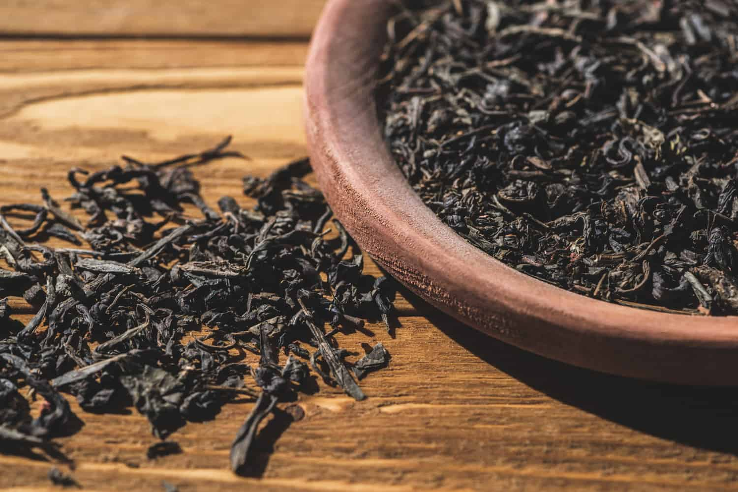 Dried black tea on wooden table in kitchen