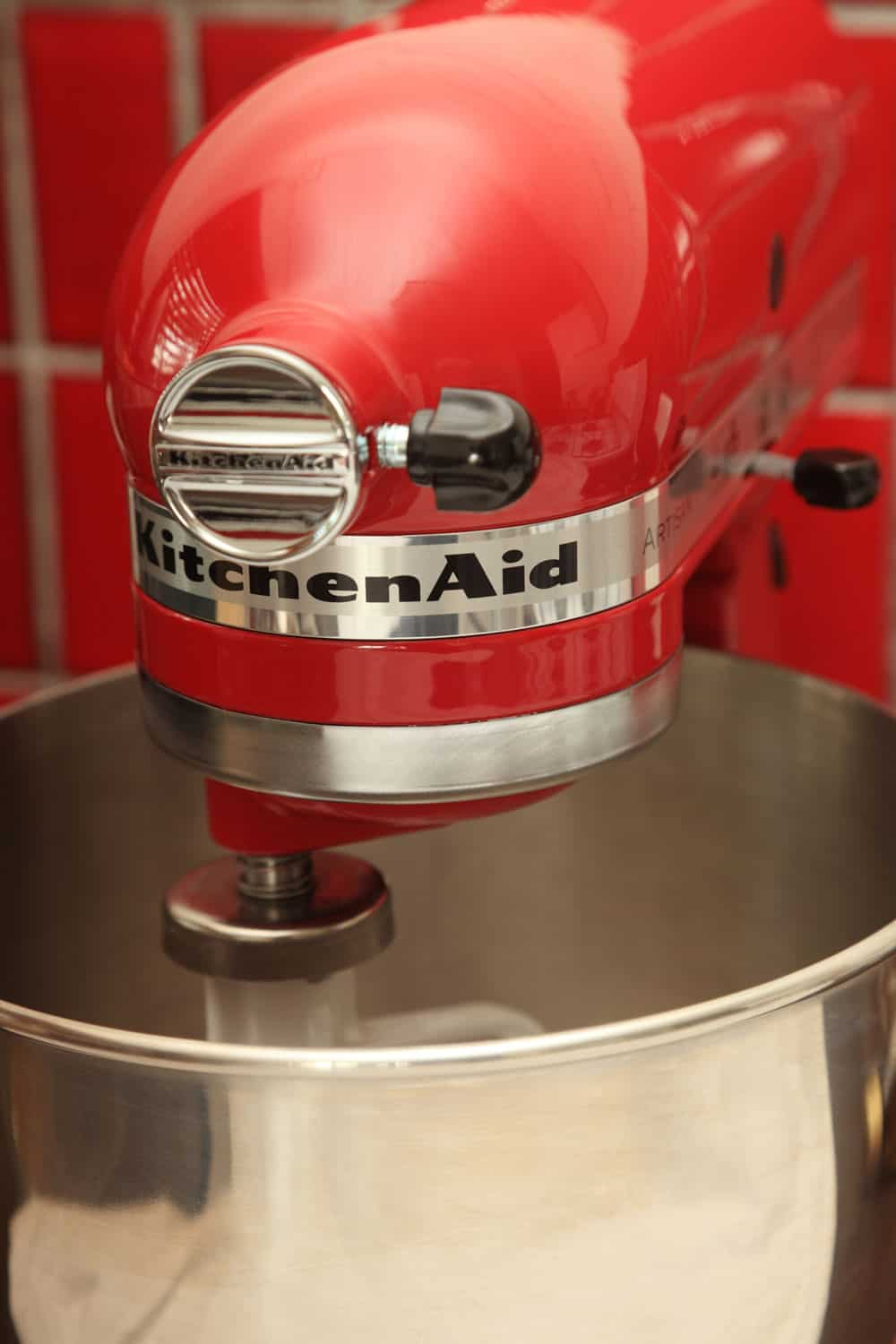 Empire Red coloured Kitchenaid Artisan Stand Mixer, angled front view on red tiled background with flat beater attachment and bowl