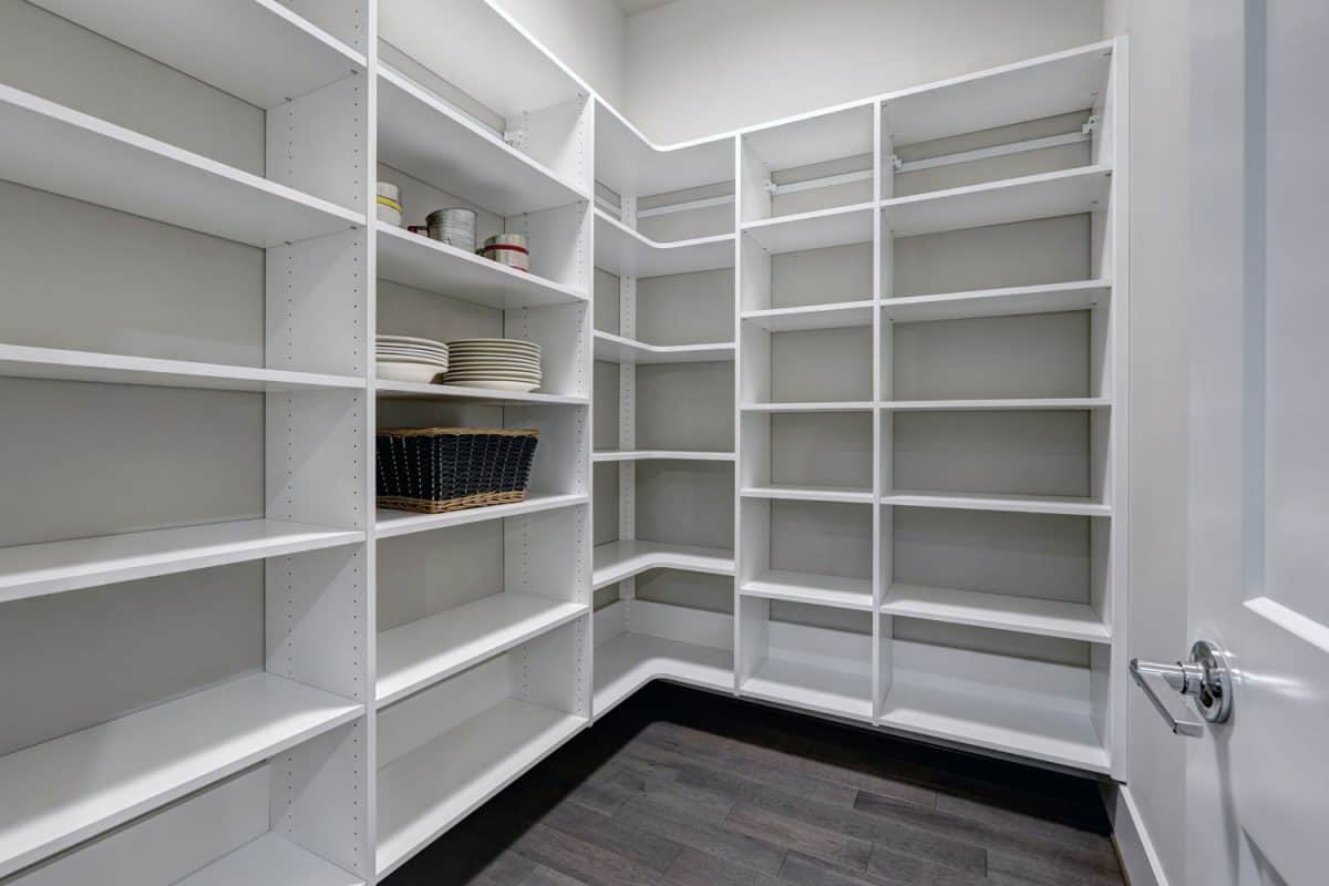 Empty pantry interior with white shelves and dark floor
