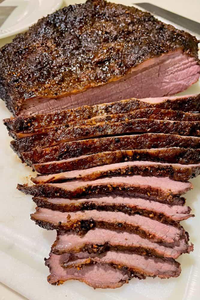 Evenly cut medium rare beef brisket on a chopping board