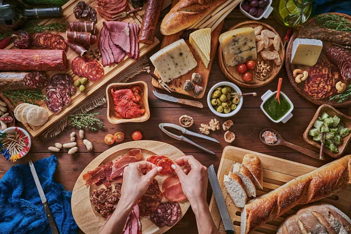 Female hands preparing snacks and appetizers in a set full of assorted cured ham and cheese on rustic wood
