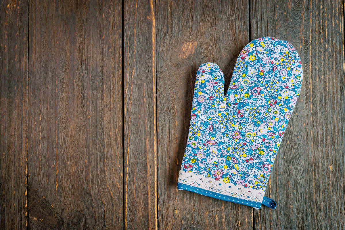 Floral oven mitten on wooden table. 9 Types Of Oven Mitts [And How To Choose]
