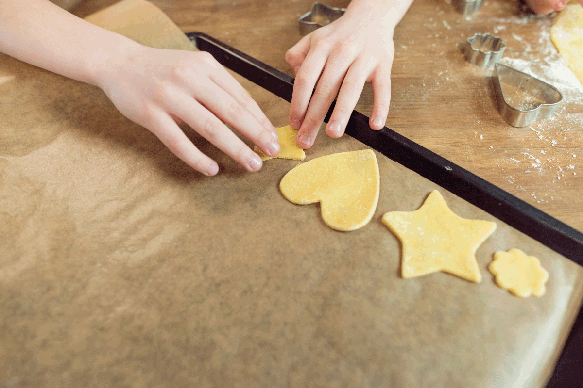 Kids making shaped cookies placing them in cookie sheet for baking. Jelly Roll Pan Vs Cookie Sheet Vs Baking Sheet - What Are The Differences