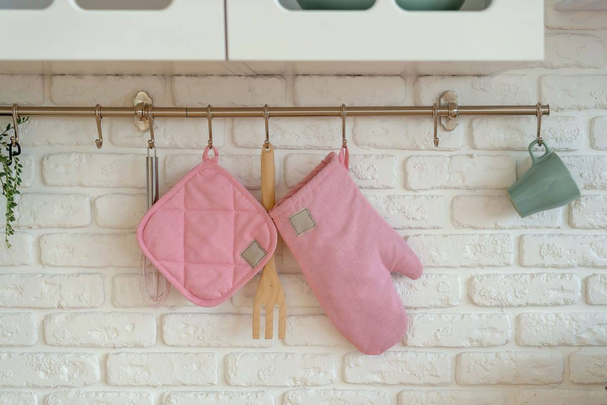 Kitchen glove, potholder, oven protection are hanging over white brick wall, 12 Types of Pot Holders [And How To Choose]