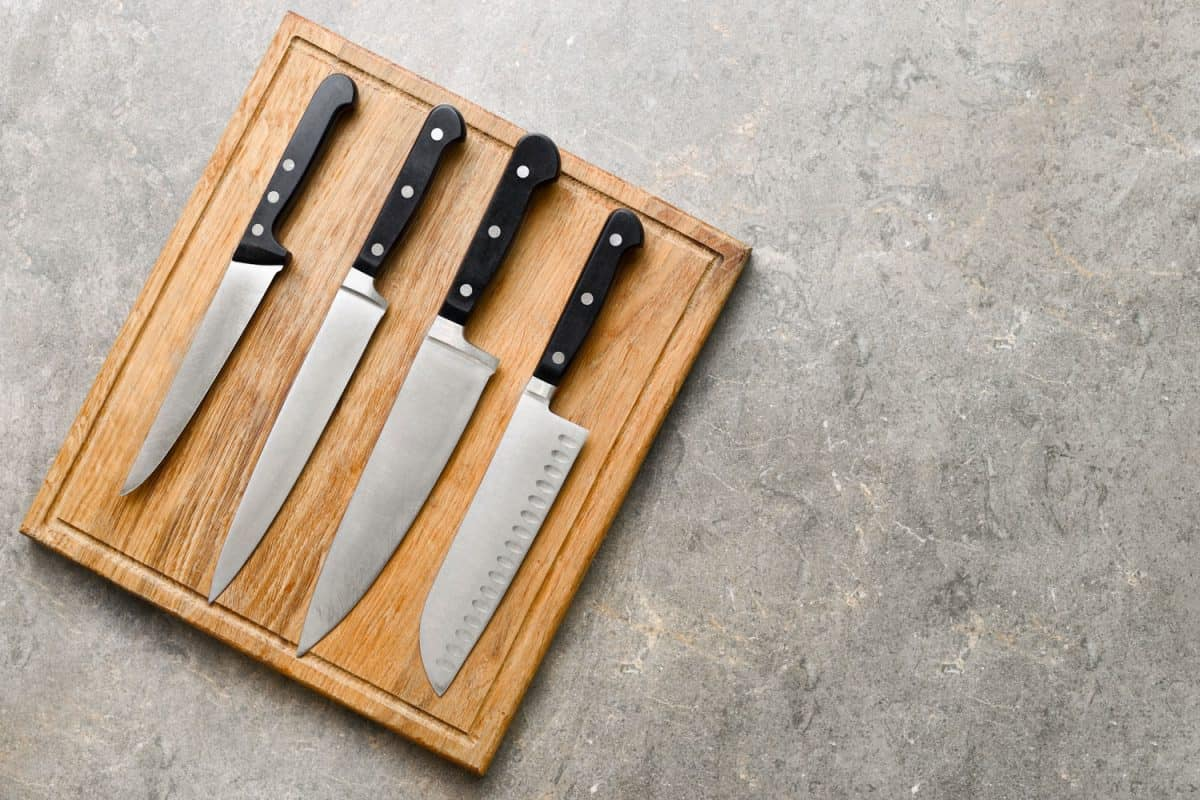 Kitchen knives set laying on wooden cutting board, flat lay, view from above, Which Knives Are Better: Wusthof Or Zwilling?
