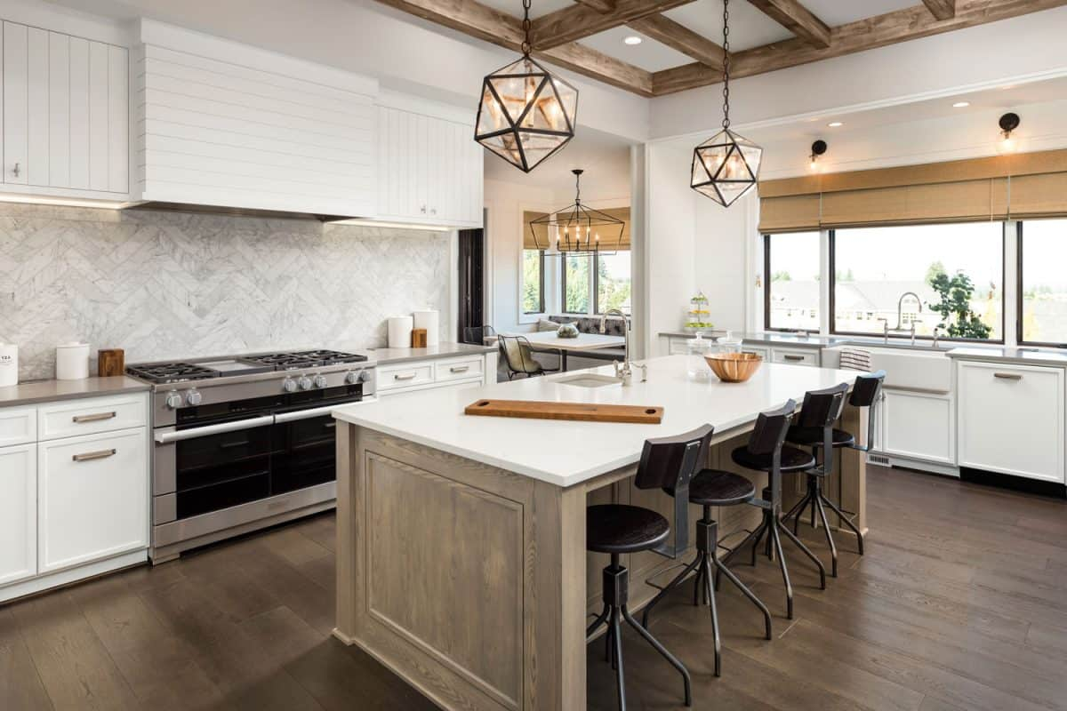 Luxurious and rustic designed kitchen interior with wooden flooring, white cabinetry, and a kitchen island with pendant lighting