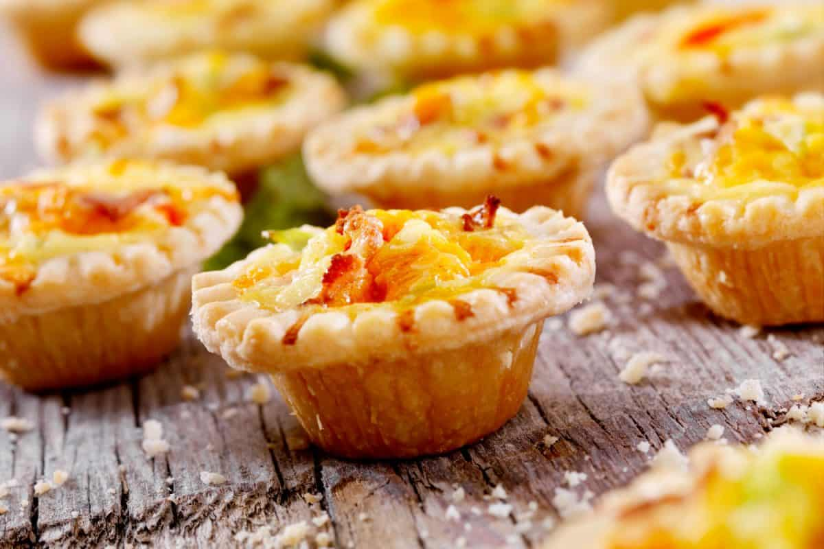 Mini quiche pies made using bacon and cheddar cheese