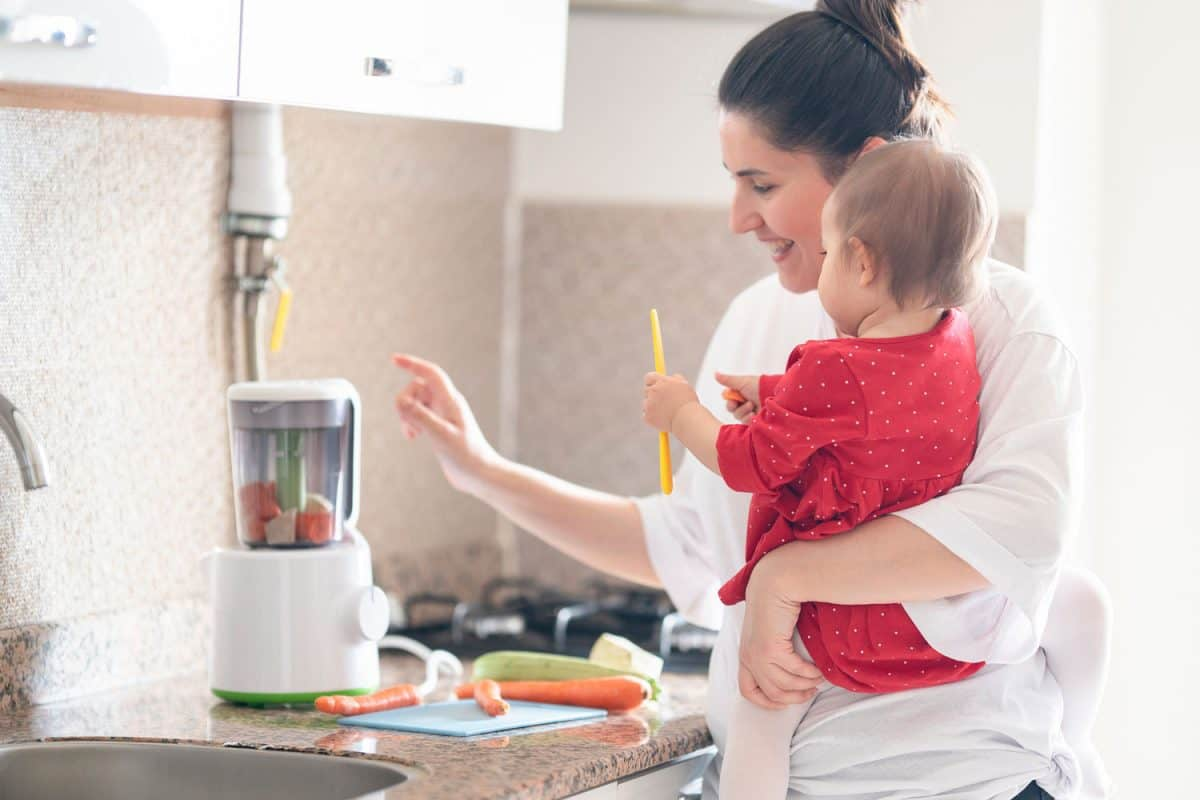 Mother is showing a blender to her little daughter. Little daughter is watching to blender., Is A Blender Good For Making Baby Food?