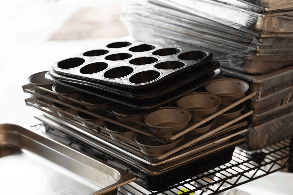 Muffin baking trays stacked in storage. How To Organize Baking Pans [7 Options To Consider]