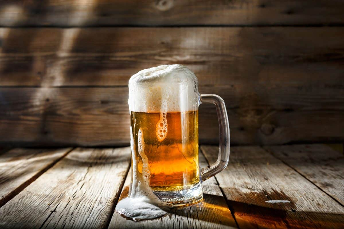 Mug of light beer with foam on a wooden table in a pub, Does The Shape Of Beer Glasses Make A Difference?