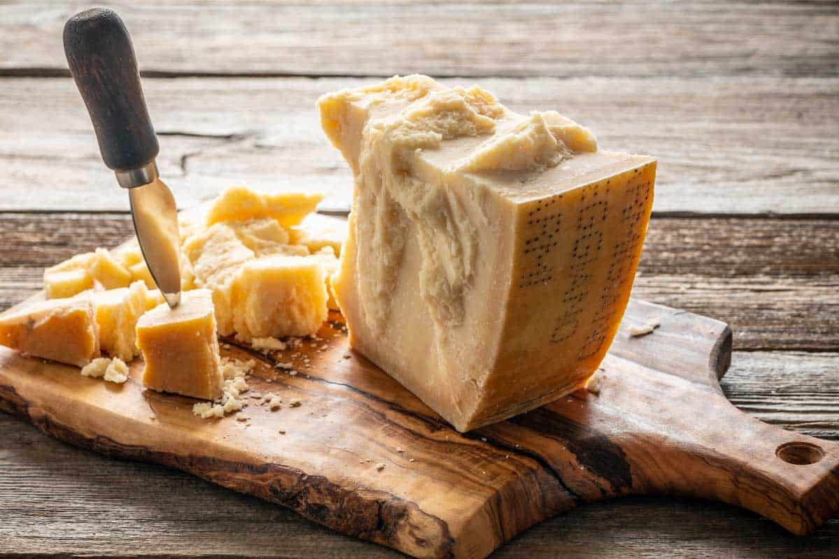 A Parmesan Reggiano cheese on cutting board and knife on wooden table, What Size Should A Cheese Board Be?