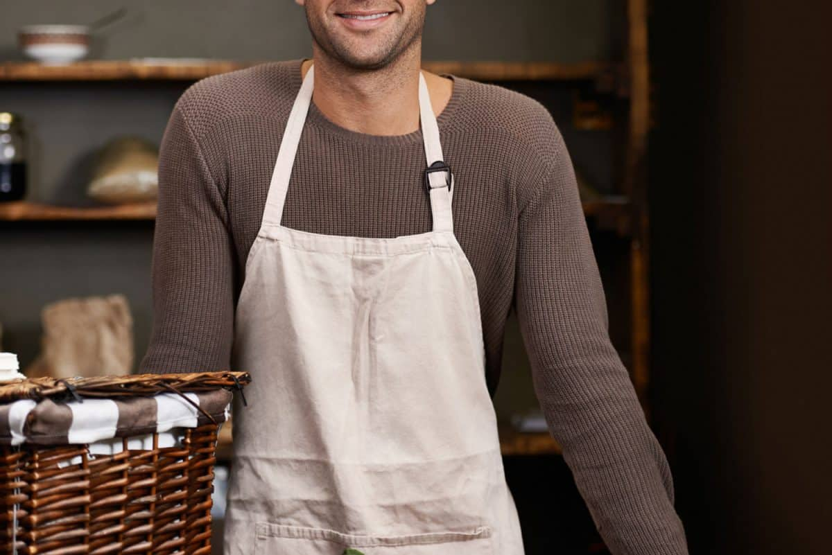 Portrait of a handsome young man standing at his food stall with a box of ingredients, Should An Apron Be Lined? [What You Need To Know]