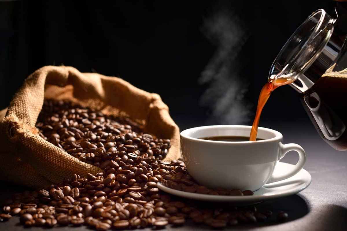 Pouring coffee to a white cup with coffee beans on the side