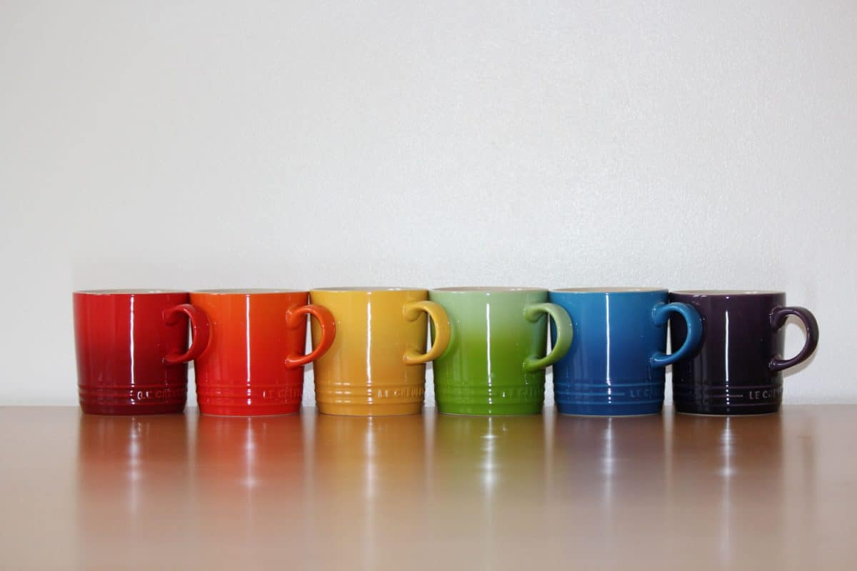 Rainbow colored Le Creuset mugs on a wooden table