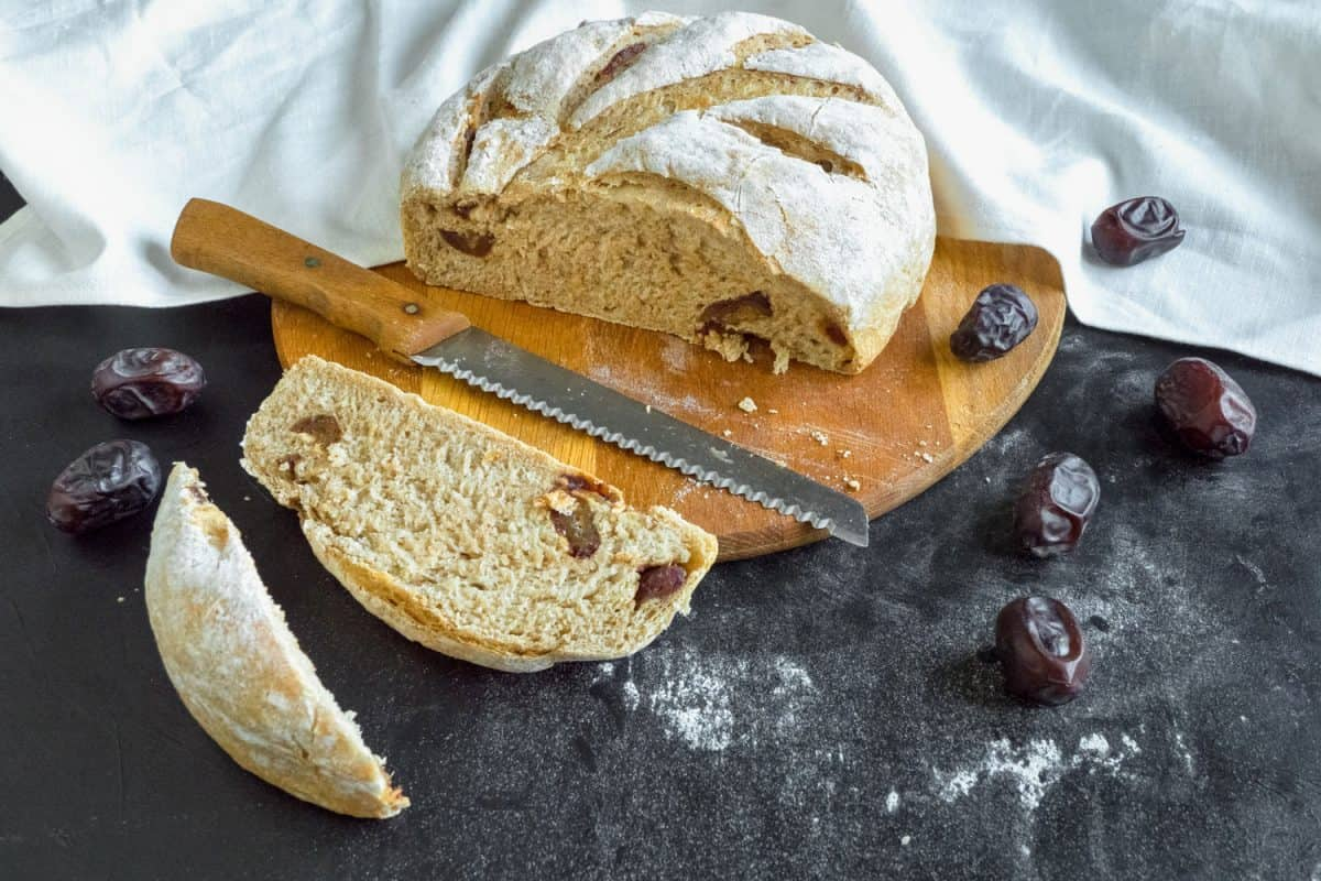 Sliced fresh bread with dates and bread knife, Do You Need To Wash A Knife After Cutting Bread? [And Other Care Tips For Bread Knife]