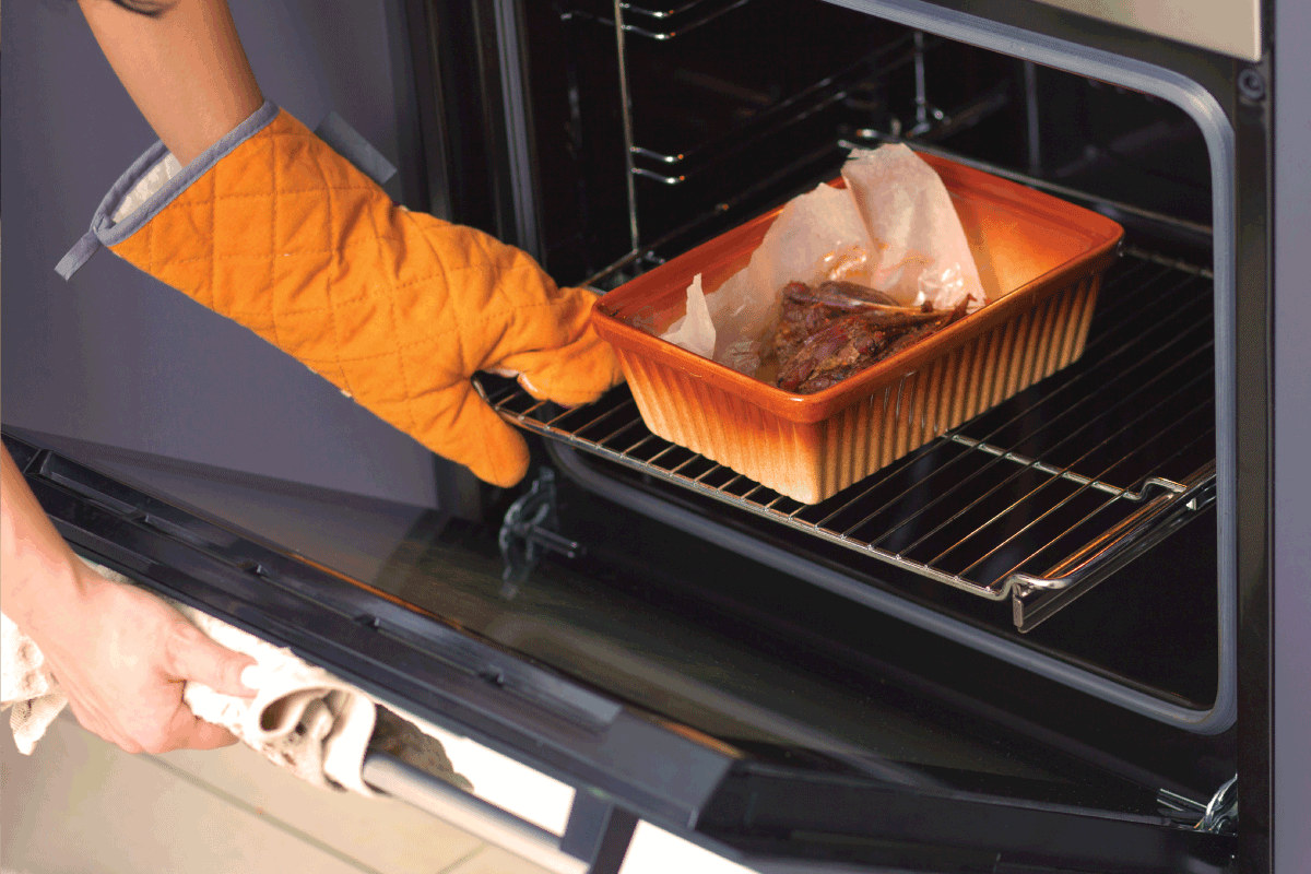 duck meat is baked in the oven on a ceramic baking sheet. Hands of a girl put baking inside the oven. Are Oven Mitts Flammable