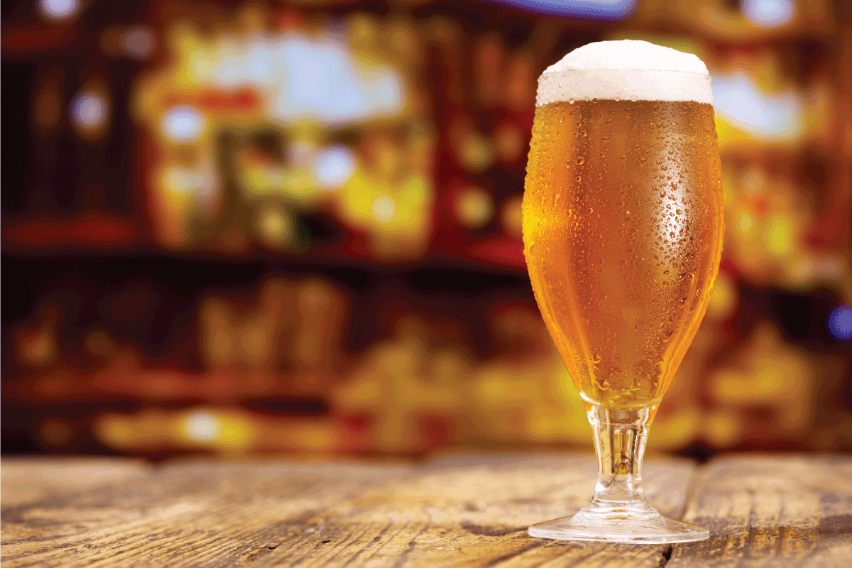 glass of beer bubbling on top of bar. Are Beer Glasses Dishwasher Safe [And How To Wash Them]
