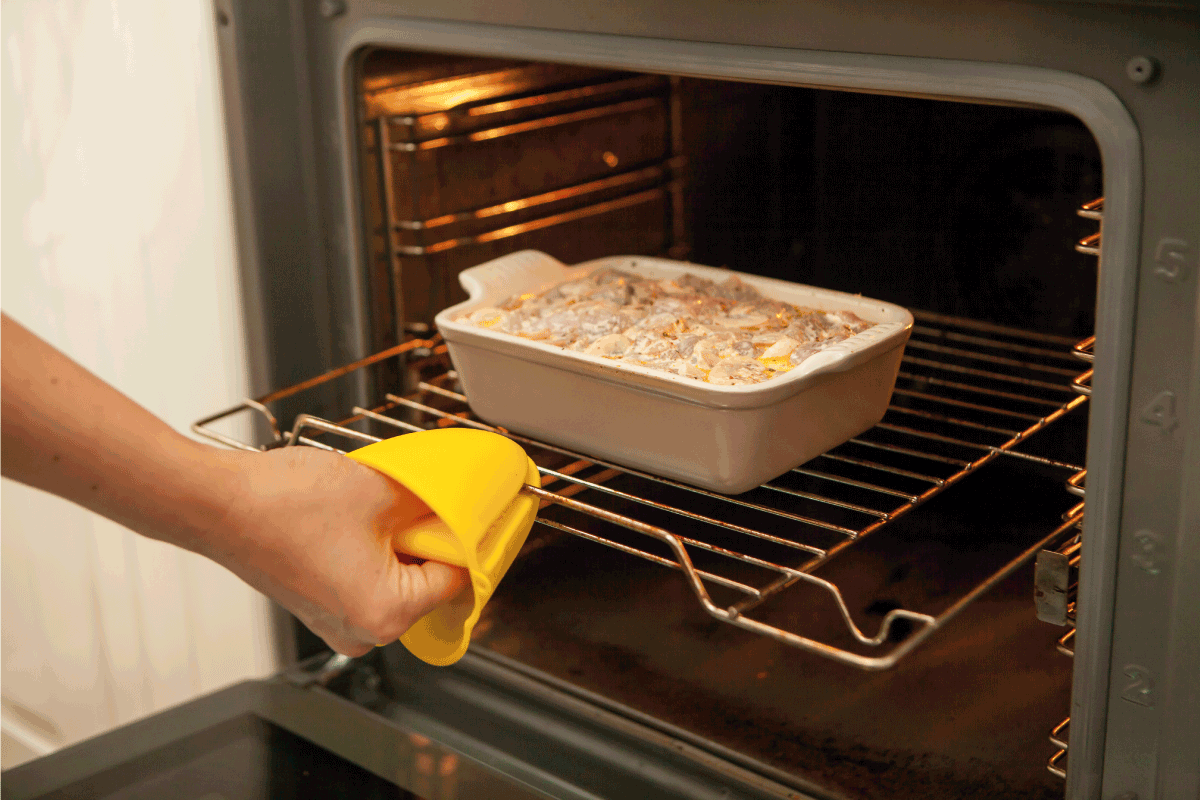 silicone glove for kitchen, woman pulling out casserole from oven using silicone mitts. Are Silicone Oven Mitts Better