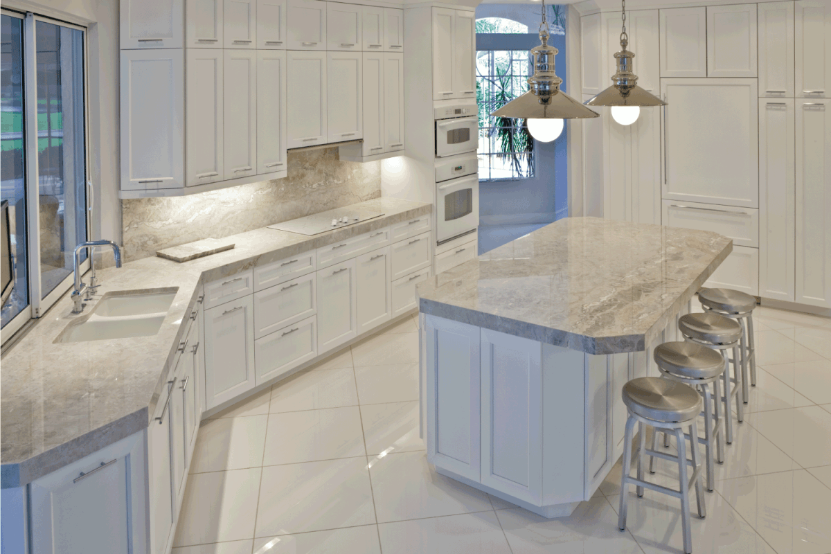 A bright, light, open and large contemporary kitchen. white floor tile, countertop, sink area