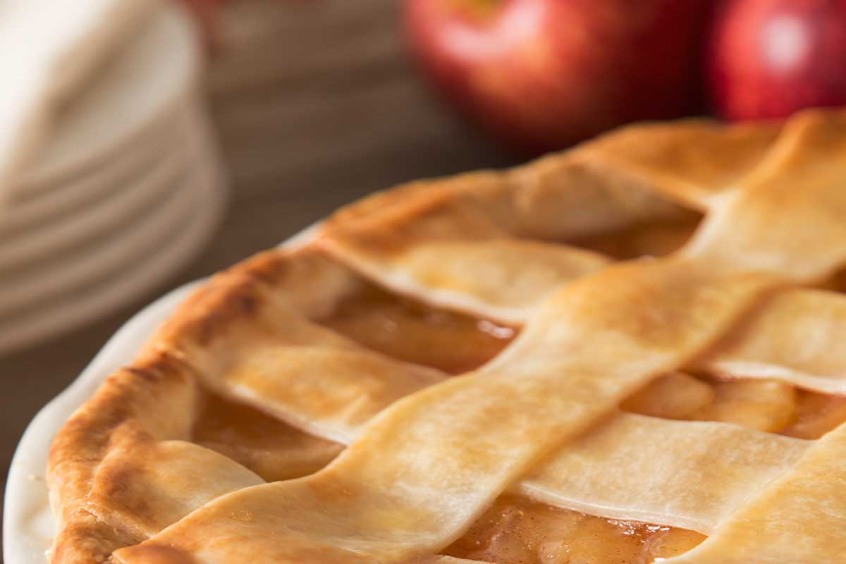 A lattice apple pie with apples on the table, Does Apple Pie Freeze Well?