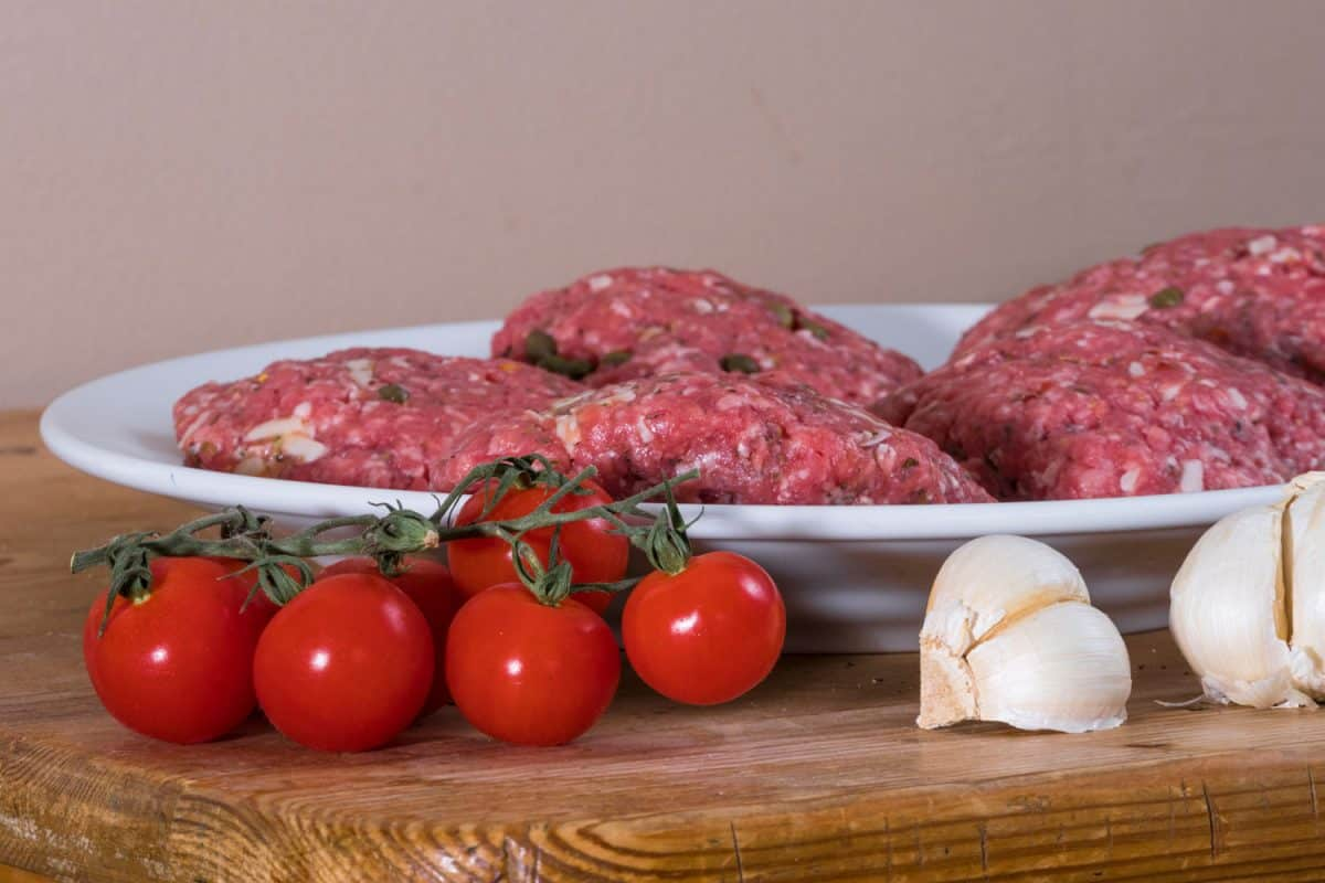A plate with mixed ground beef and other spices for a burger patty with cherry tomatoes on the side and garlic