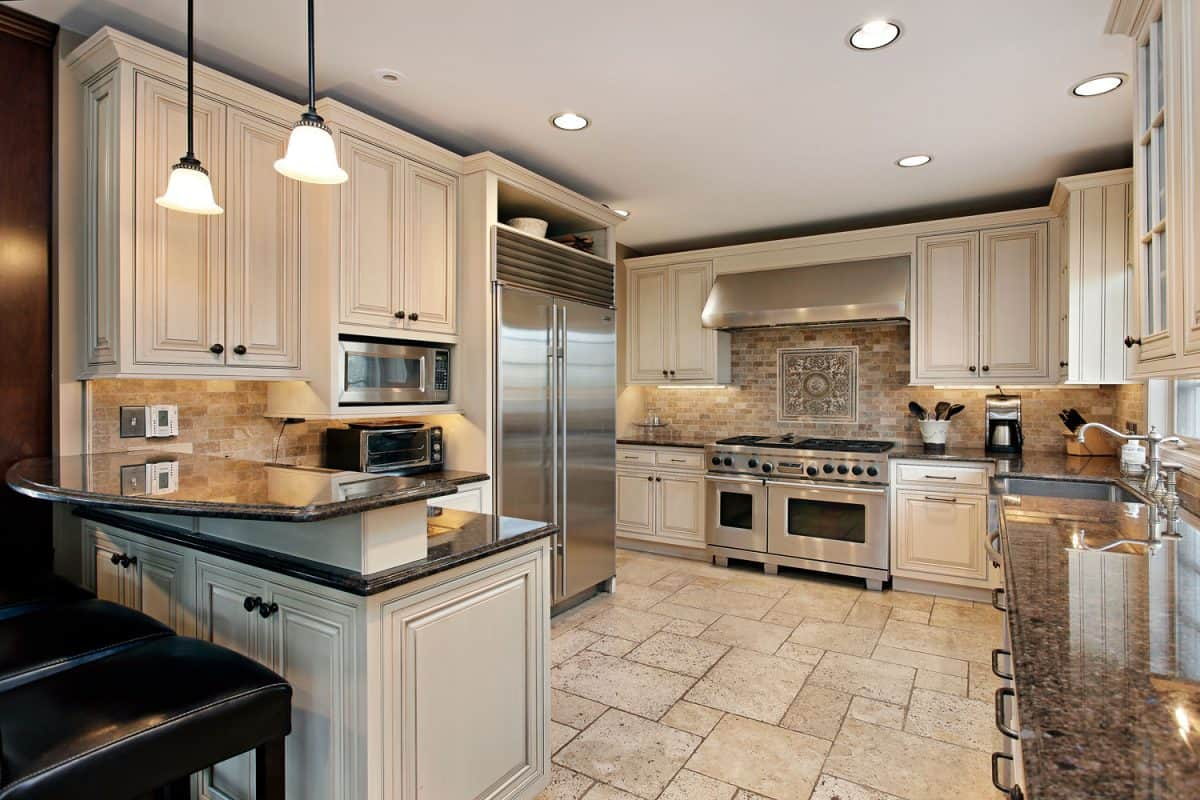 A small modern interior kitchen with off white painted cabinets, recessed lighting, and black countertops