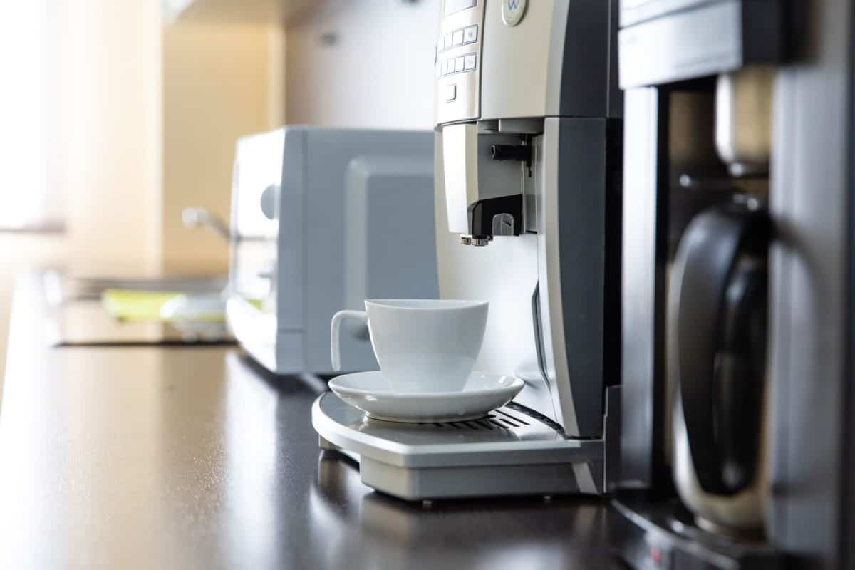 An expensive looking coffee maker pouring coffee on a small cup, Do Keurig Machines Grow Mold?