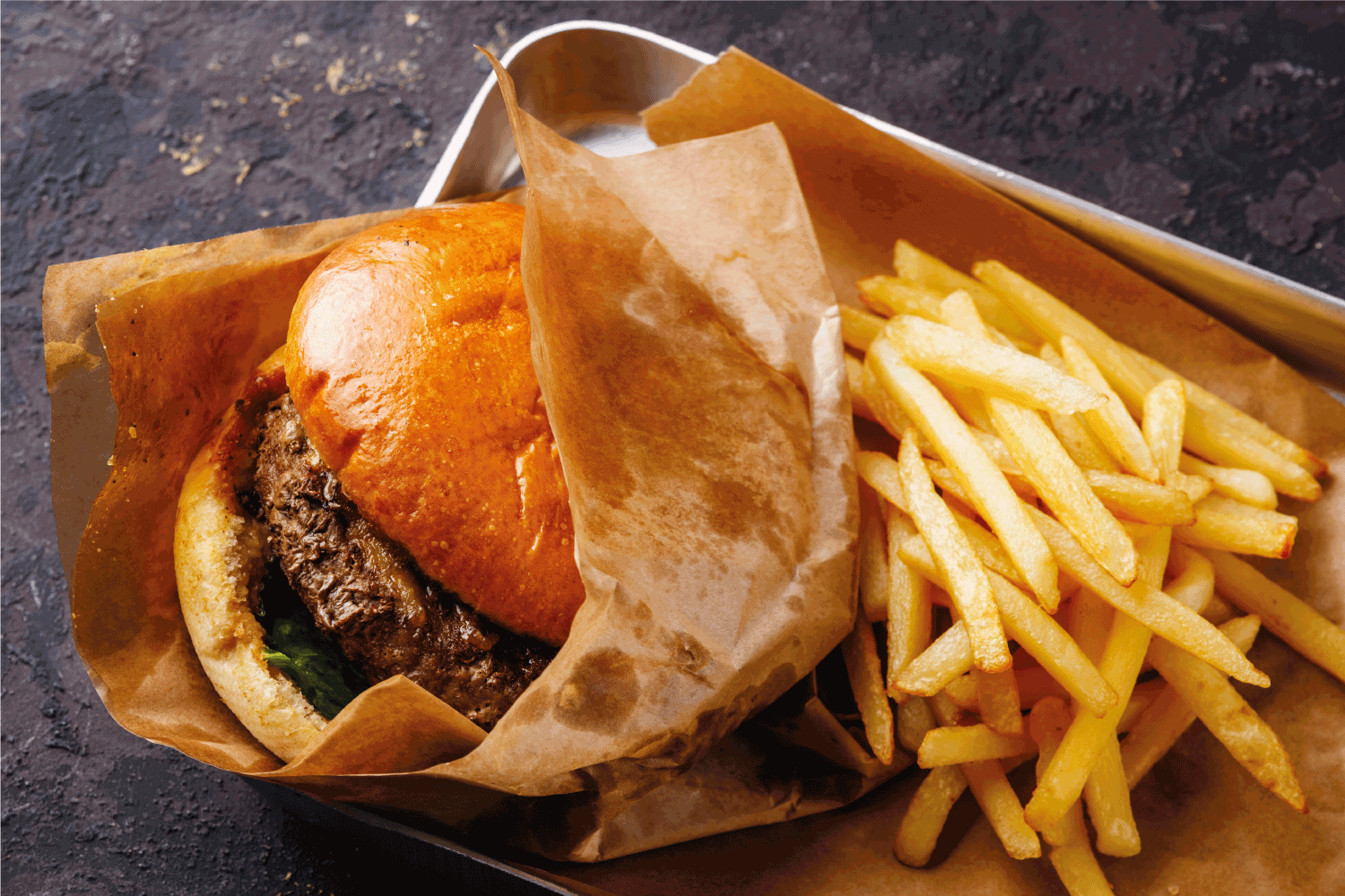 Burger with meat and French fries in aluminum tray on dark background