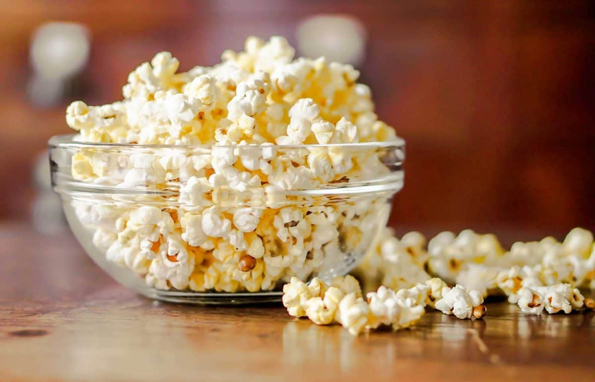 Close up of popcorn in a glass cup on a wooden table