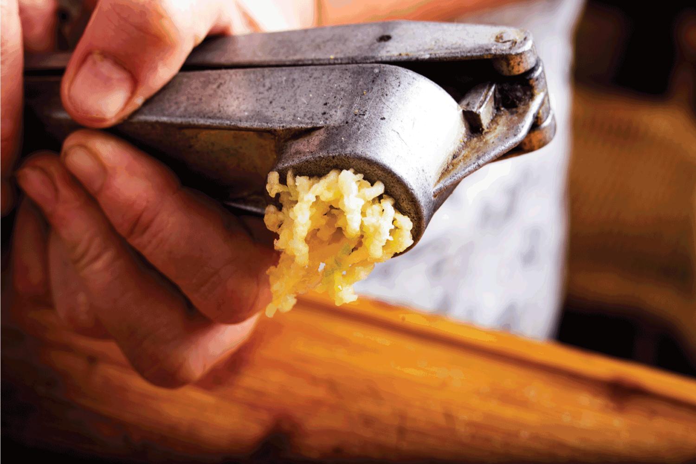 Crushing garlic with a garlic press in the kitchen.