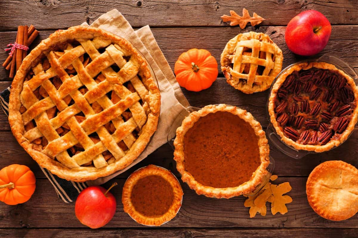 Different sizes of apple pies with apples and pumpkins on the table, Does Apple Pie Need A Top Crust?