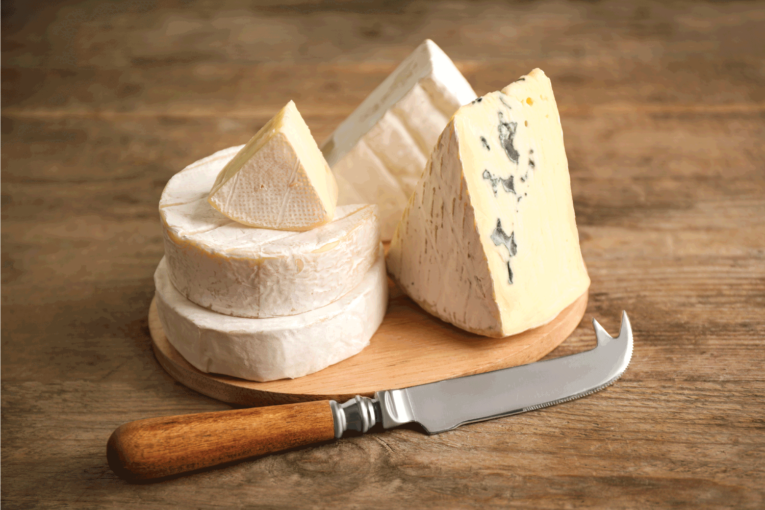Different types of cheese and knife on wooden table with pronged cheese knife