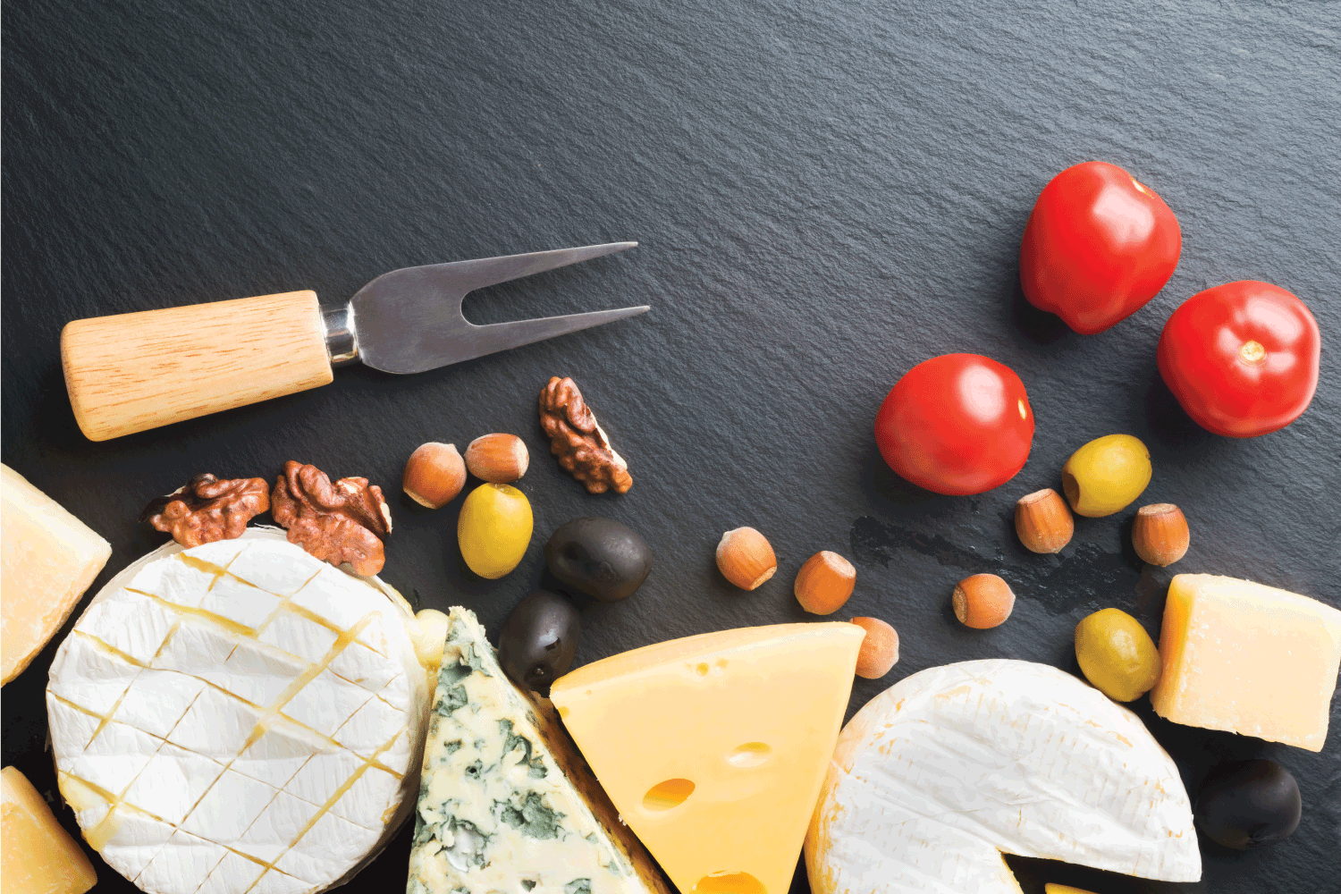 Different varieties of cheese, tomatoes and nuts with cheese fork