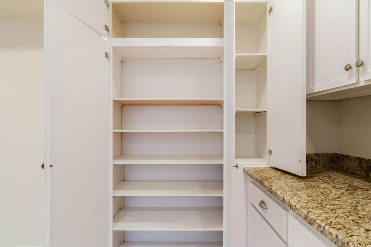 Empty pantry shelves next to a marble countertop kitchen , Can You Combine A Pantry And Laundry Room?