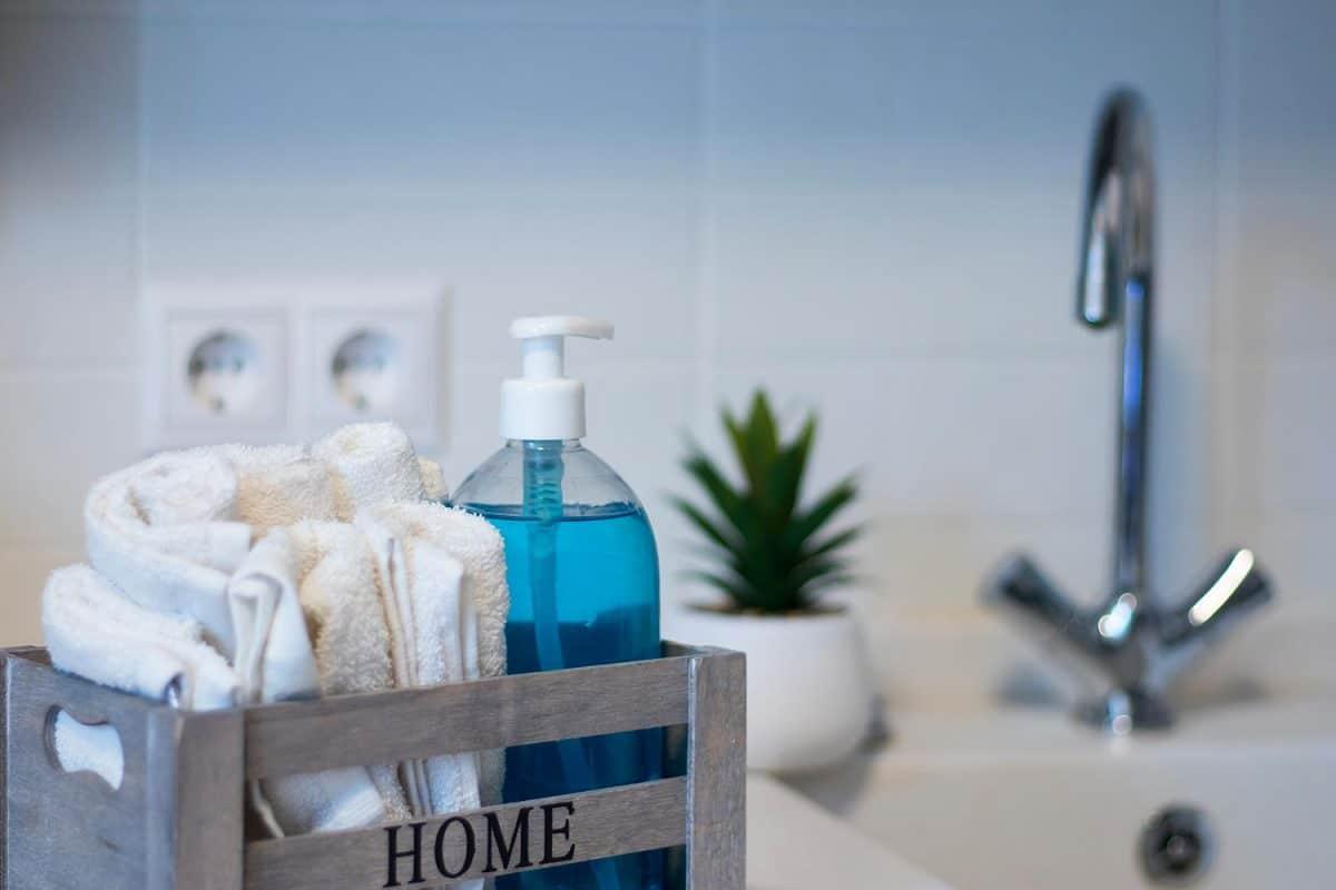 Liquid blue soap in a transparent plastic dispenser beside hand towel