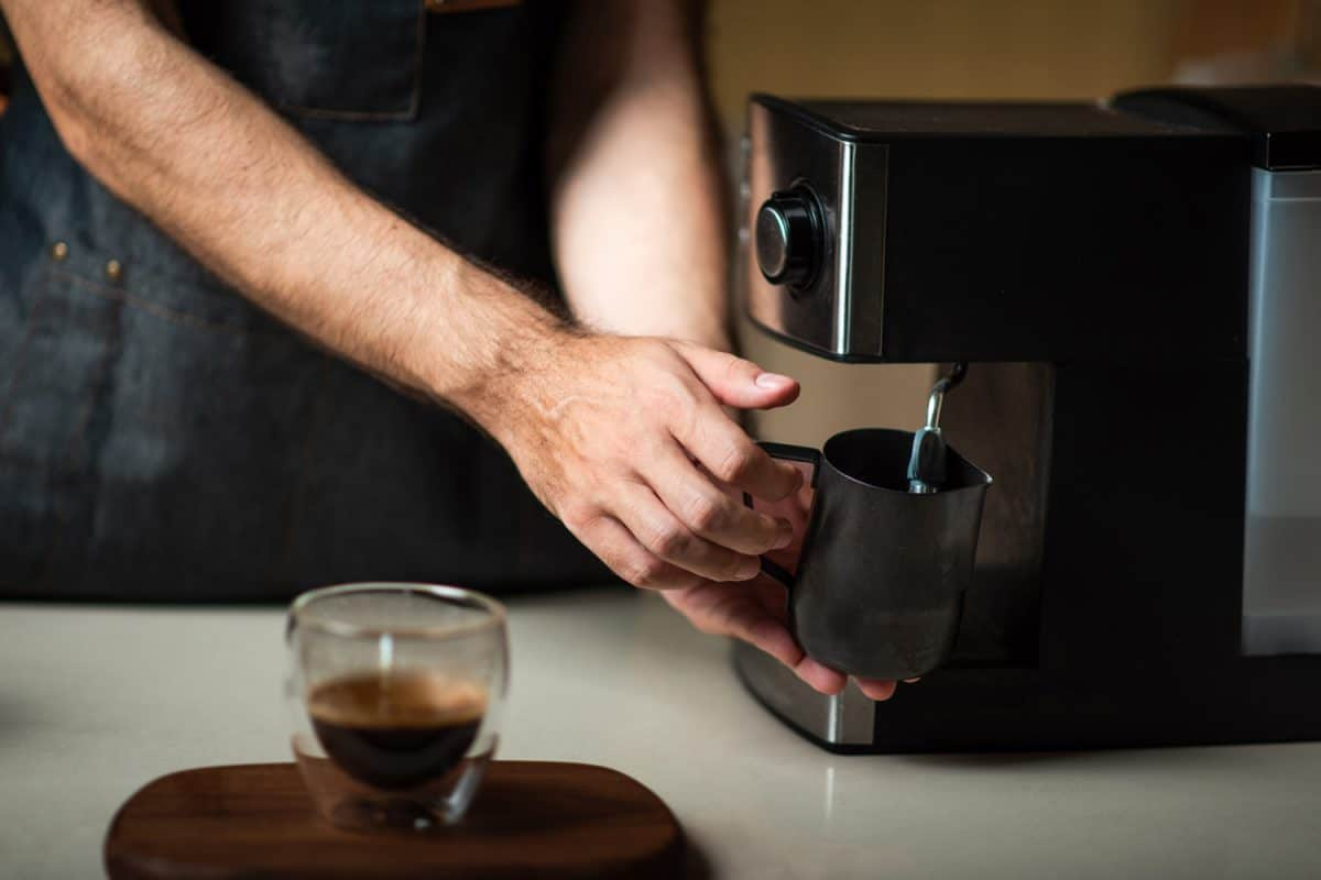 Male barista steaming the milk in a metal jar for making cappuccino coffee drink close up, Should You Leave A Keurig Plugged In?