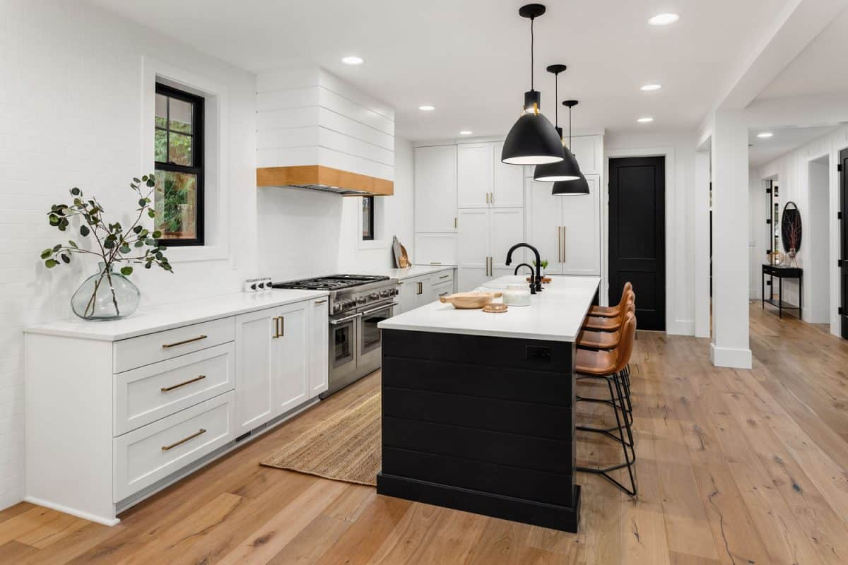 Modern white contemporary kitchen with white painted cabinetry and wooden flooring