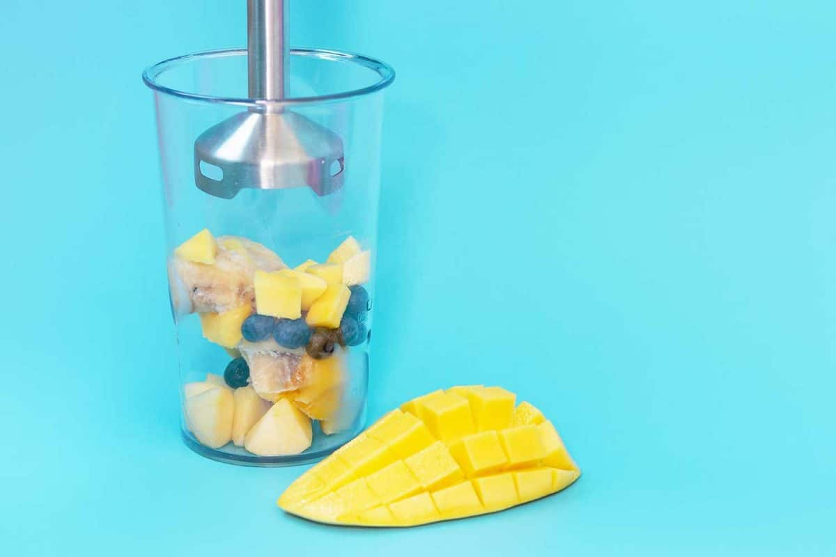 Plastic bowl with fruit and immersion blender on blue background close-up