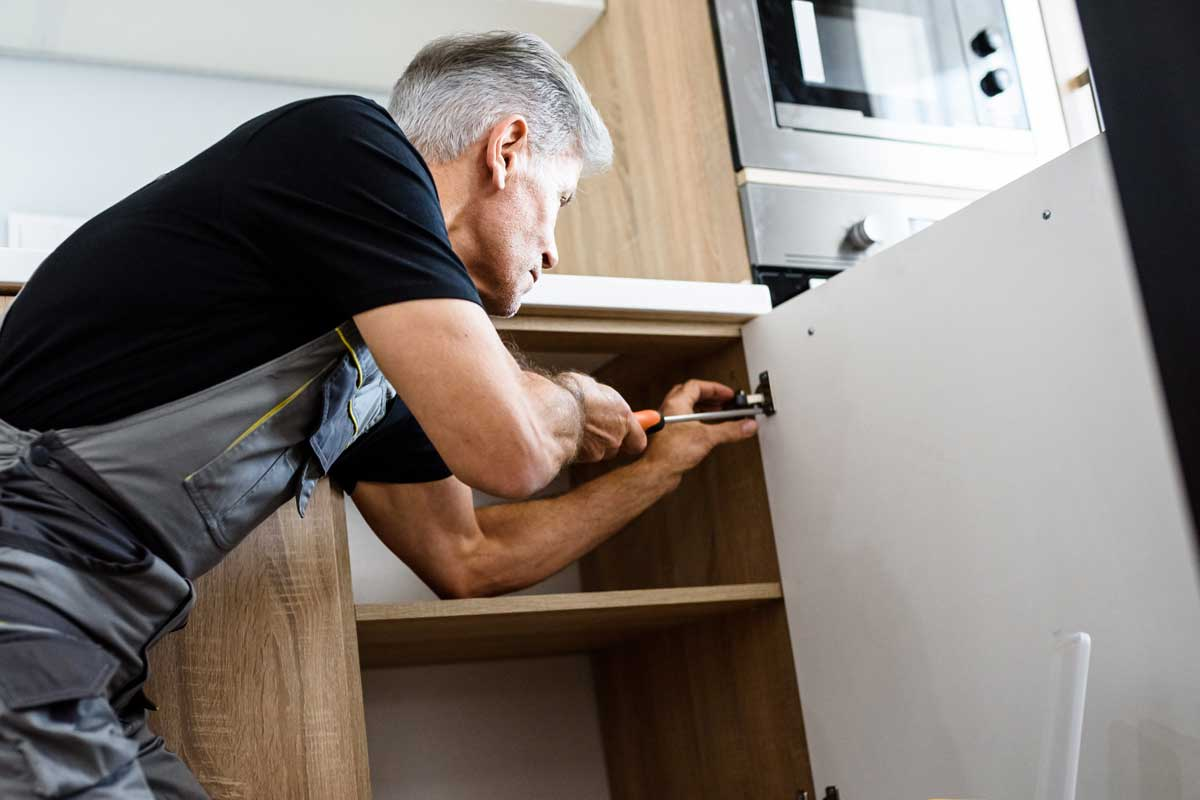 Repairman in uniform working, fixing kitchen cabinet using screwdriver, How To Restore Kitchen Cabinets And Fix Worn Spots