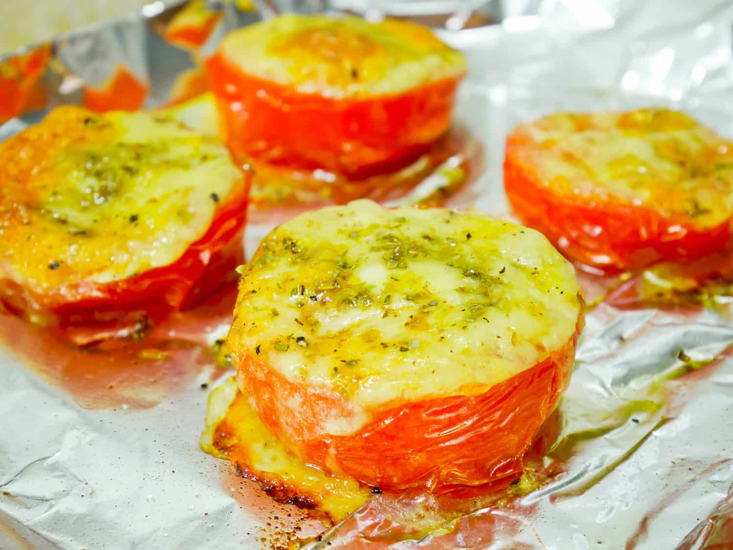 Roasted tomatoes with mozzarella cheese on aluminium foil in oven
