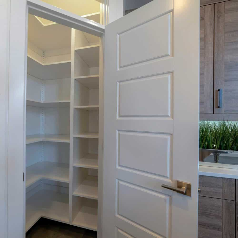 Square small pantry with empty wall shelves at the corner of the kitchen of home