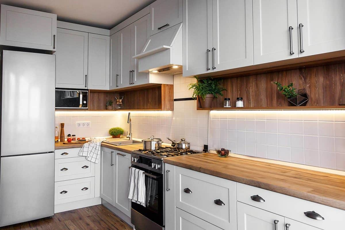 Stylish light gray kitchen interior with modern cabinets and stainless steel appliances in new home