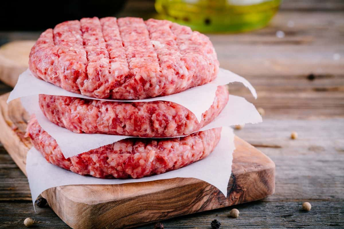 Three big slices of ground beef patty on a small wooden chopping board