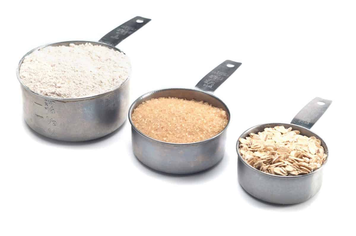 Three progressively larger measuring cups full of flour and sugar in the raw and oats