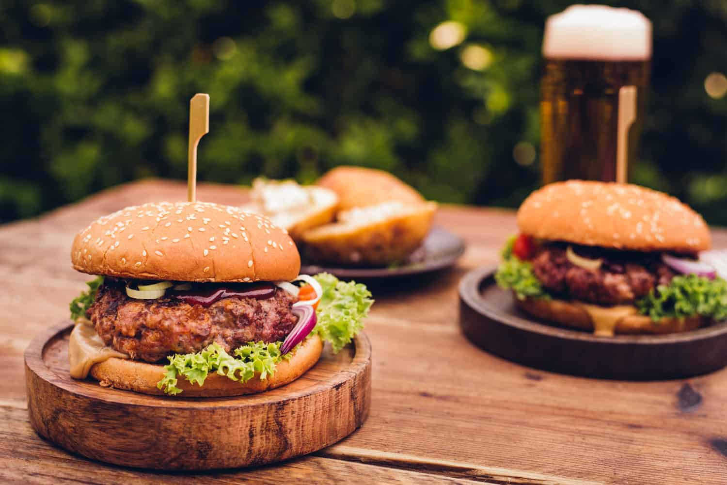 Two delicious burgers with ranch dressing, lettuce, and cheese on a small wooden plate, How To Season Hamburgers For The Grill [9 Seasonings To Try Out]