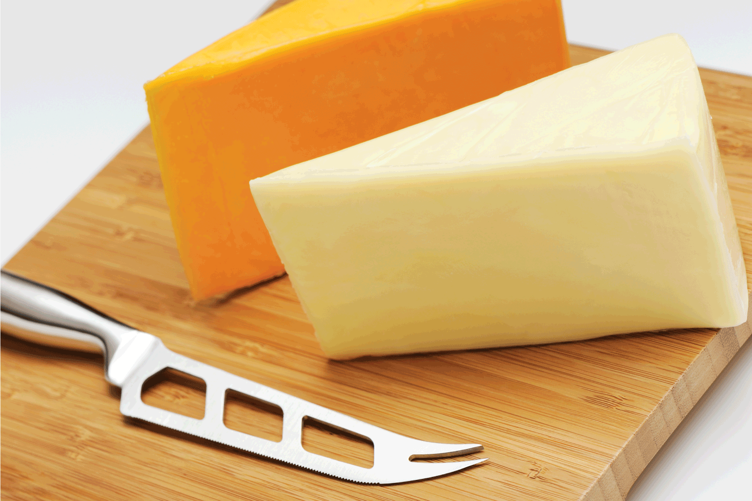Two pieces of cheddar cheese (white and yellow) on a cutting board with cheese knife.