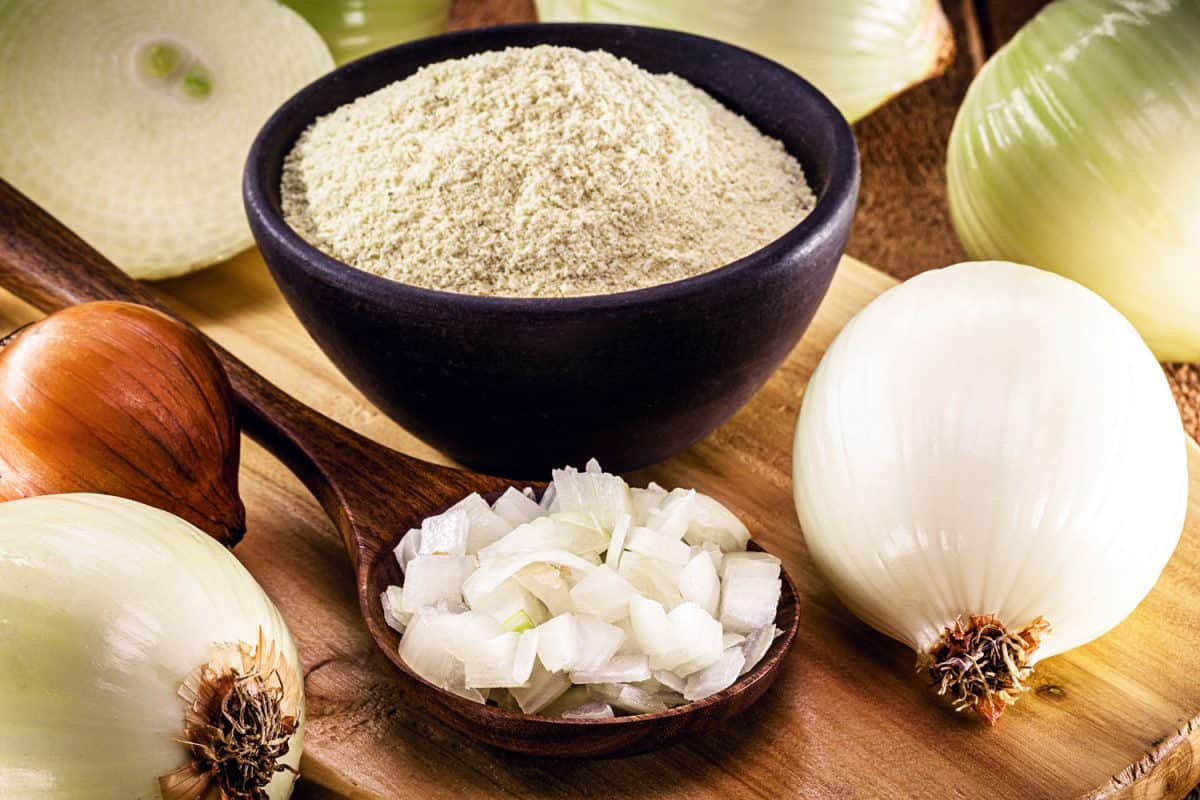 White onions and flour on top of a chopping board