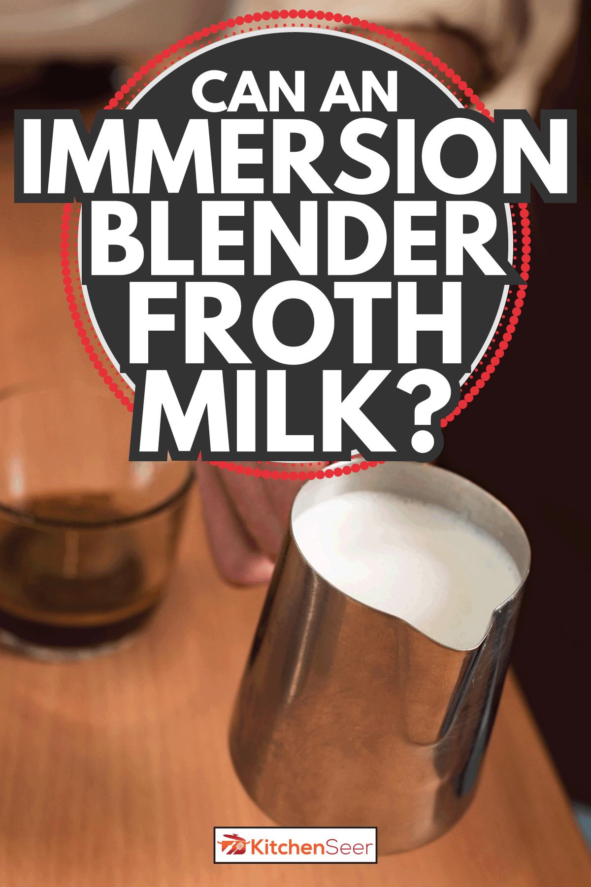 barista holding steel milk jug. Can An Immersion Blender Froth Milk