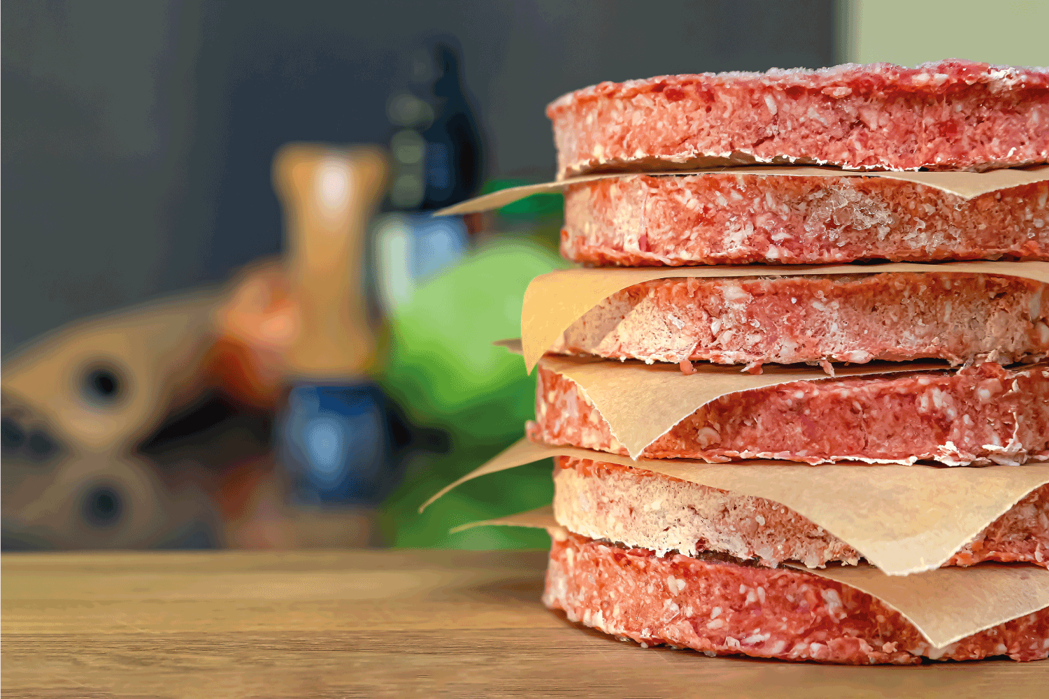 frozen beef hamburger patties, defrost before grilling, stacked on the counter.