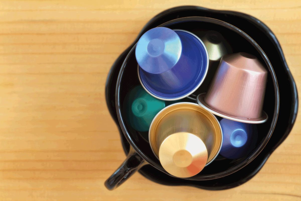 overhead photo of coffee capsules in a coffee mug on a wooden table. How Many Times Can You Use A K-Cup